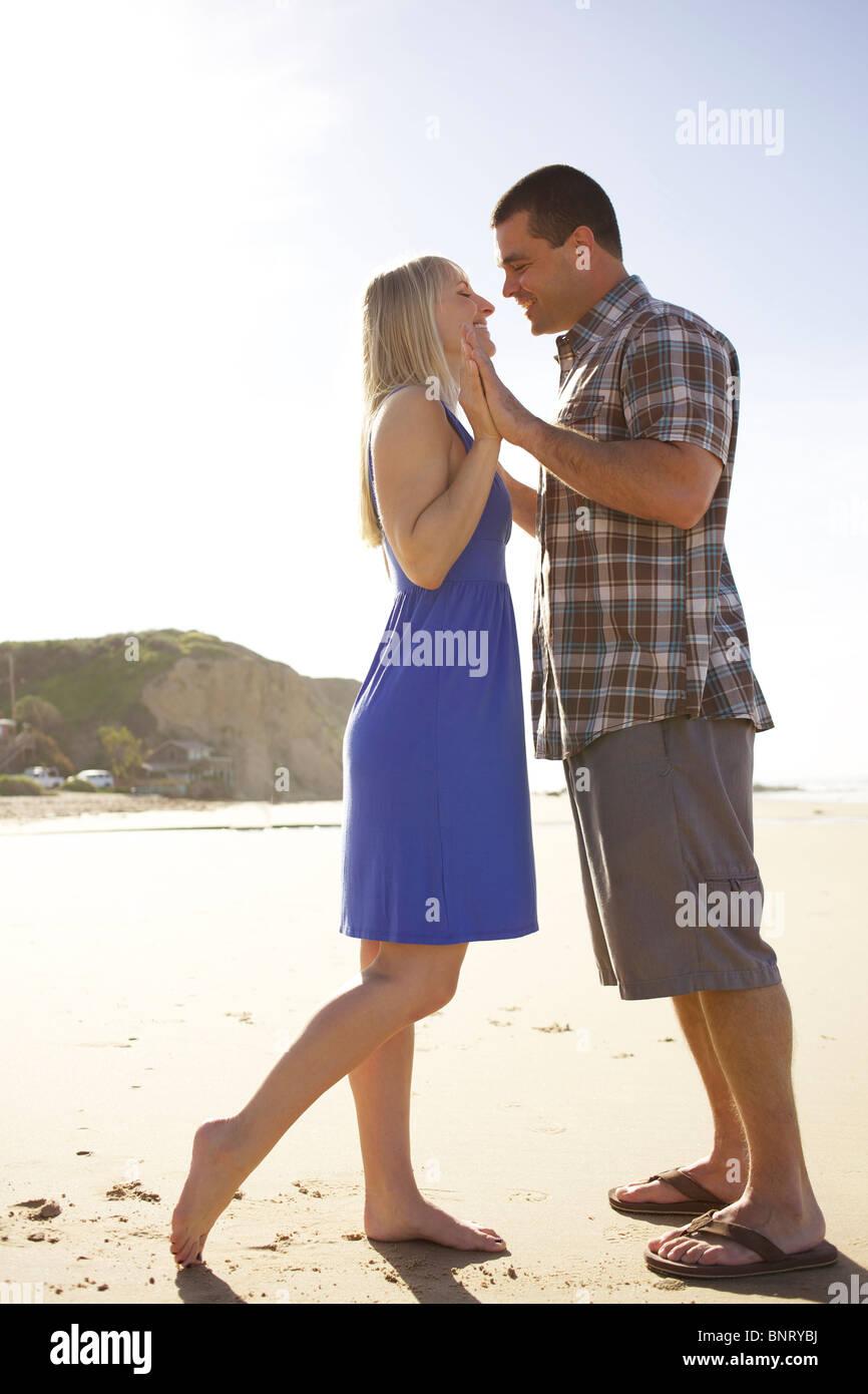Touchez deux par la main et penchez-vous pour un baiser à la plage. Photo Stock