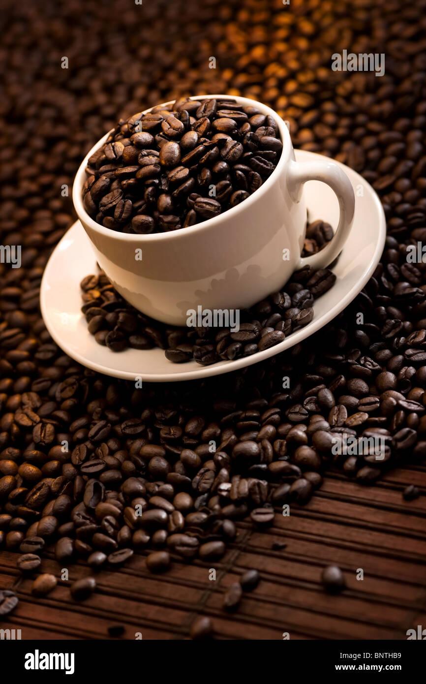 Tasse rempli de délicieux grains de café torréfié Photo Stock