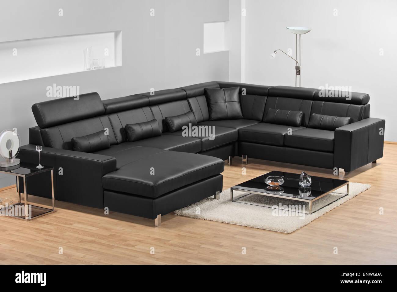 Vue d'un appartement moderne avec un canapé en cuir noir Photo Stock