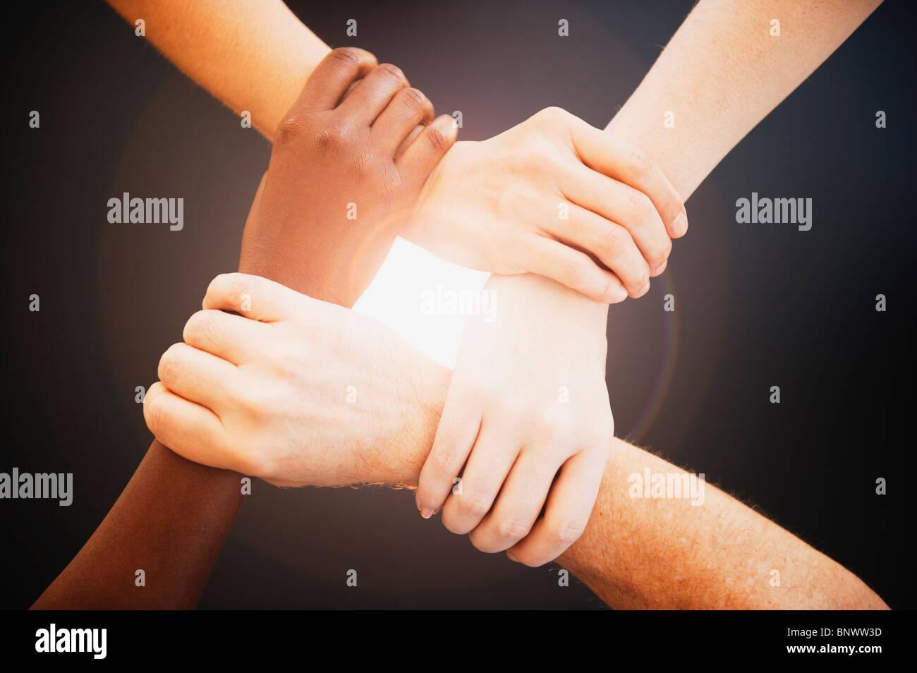 Quatre mains tenant les poignets d'autres personnes Photo Stock
