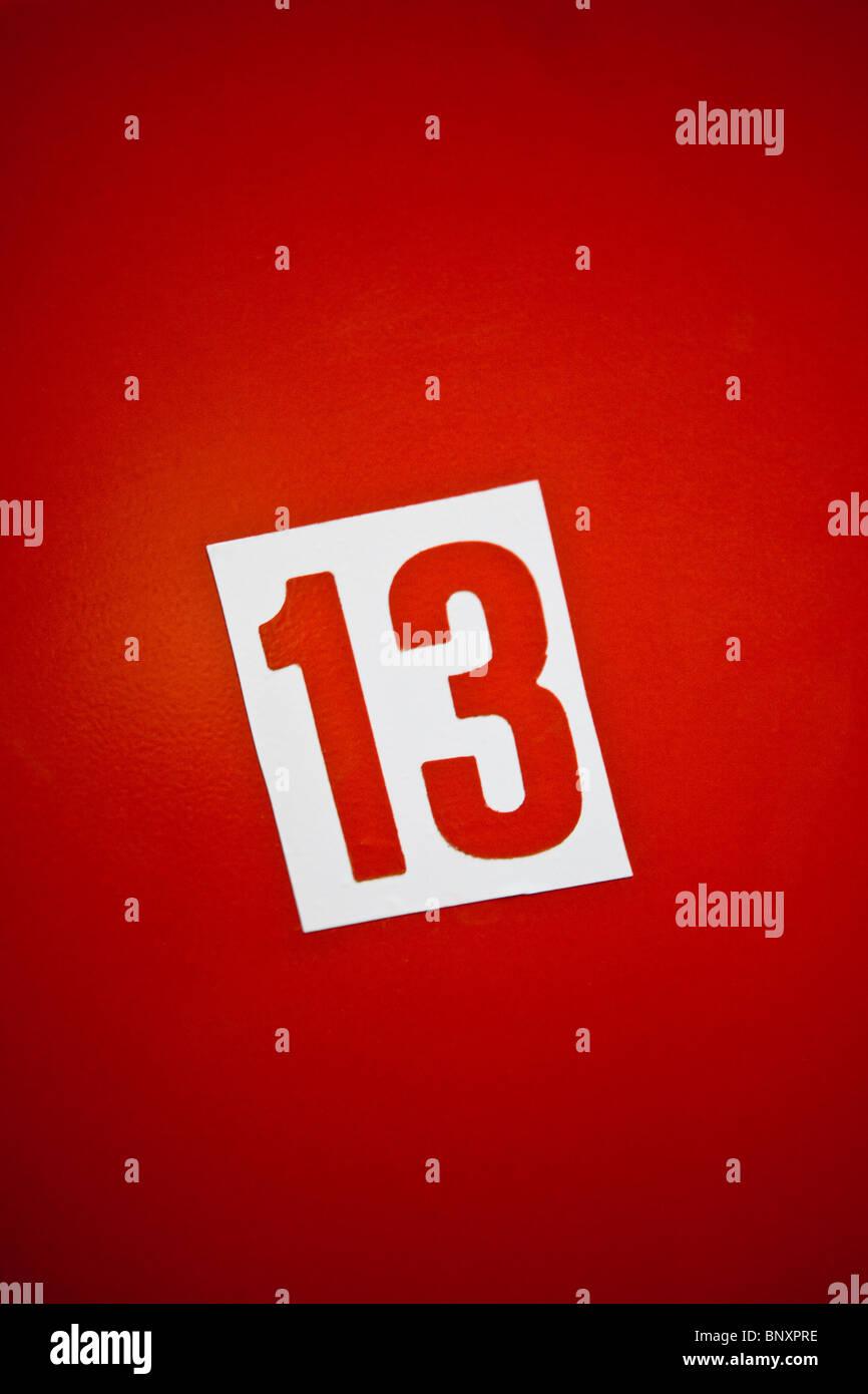 Numéro treize contre fond rouge Photo Stock