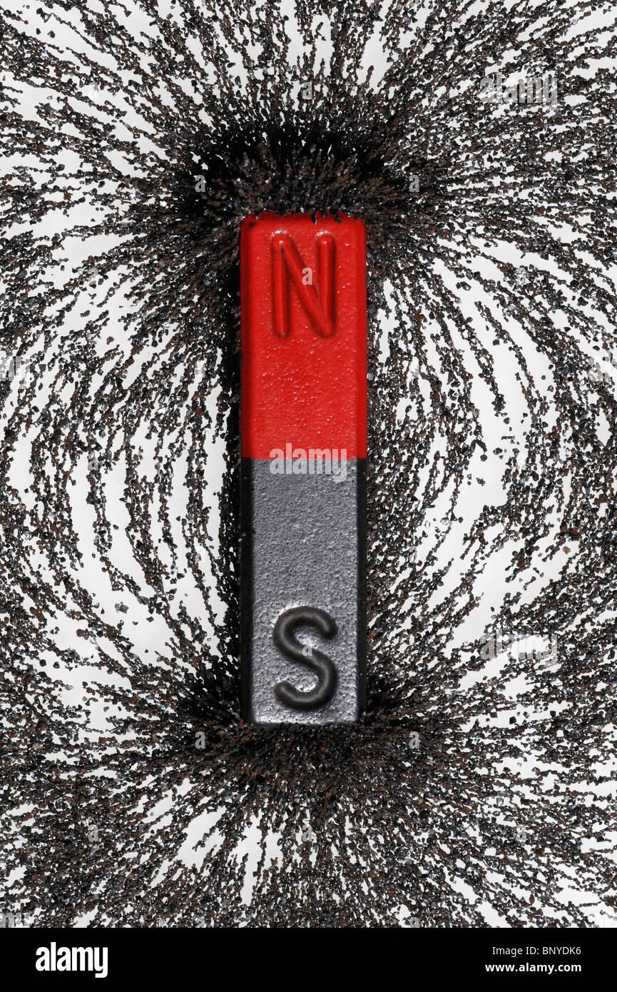 Aimant avec de la limaille de fer montrant les lignes de champ magnétique convergent vers les pôles Photo Stock