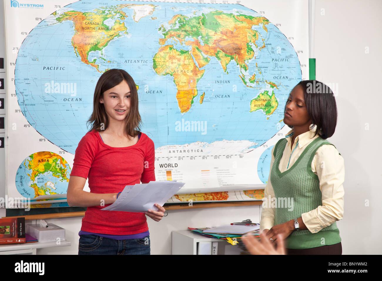 La diversité ethnique multi raciales diversifiées interracial multiculturelles adolescente donne lecture du rapport de la classe enseignant encourage personne personnes Banque D'Images