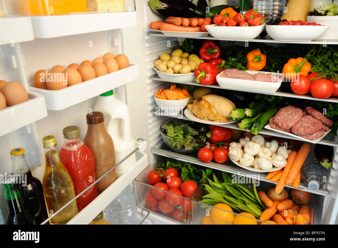 Vue à l'intérieur de réfrigérateur avec des étagères remplies de produits frais Photo Stock