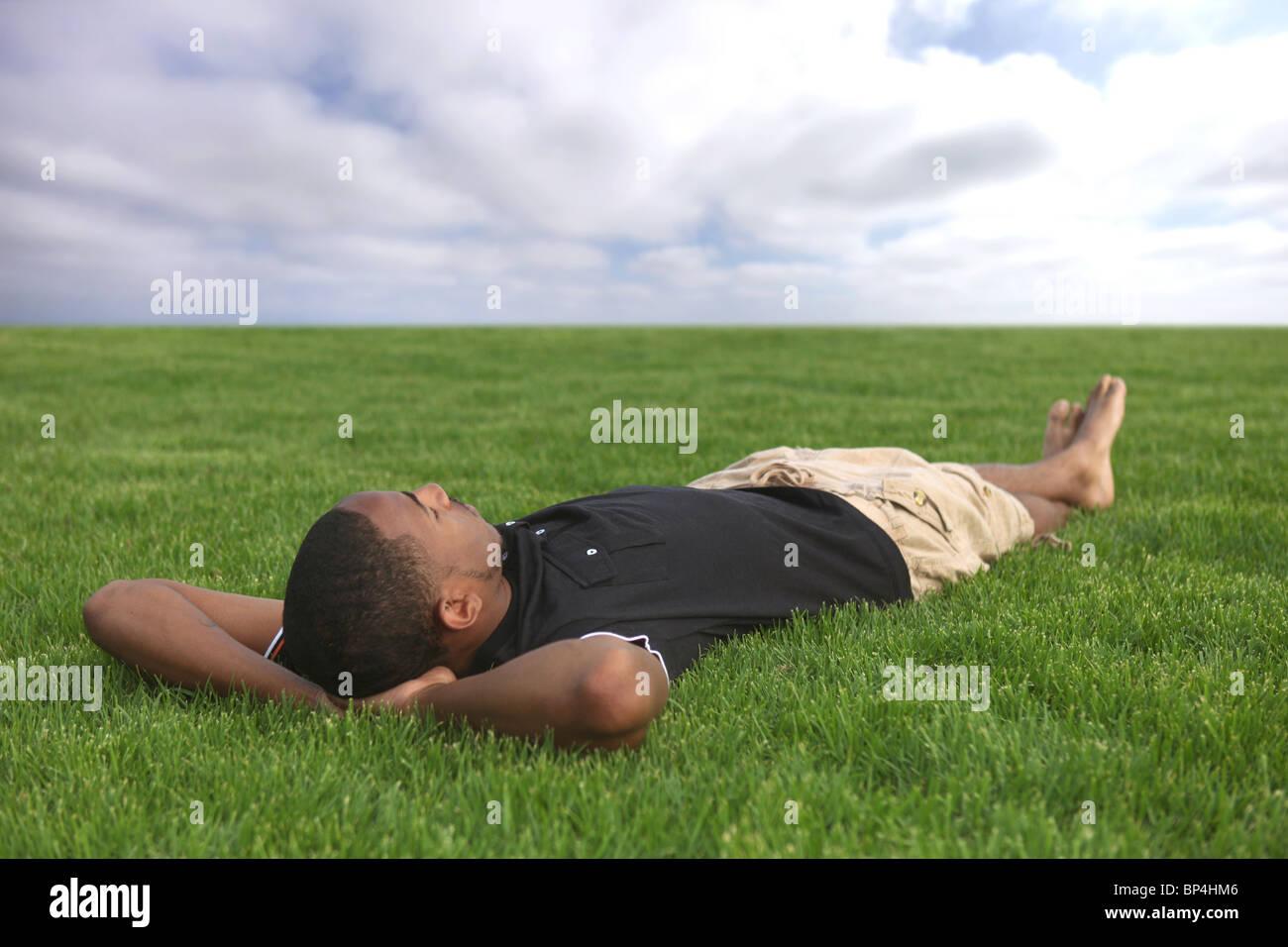 African American Male Student reposant dans l'herbe en plein air Photo Stock