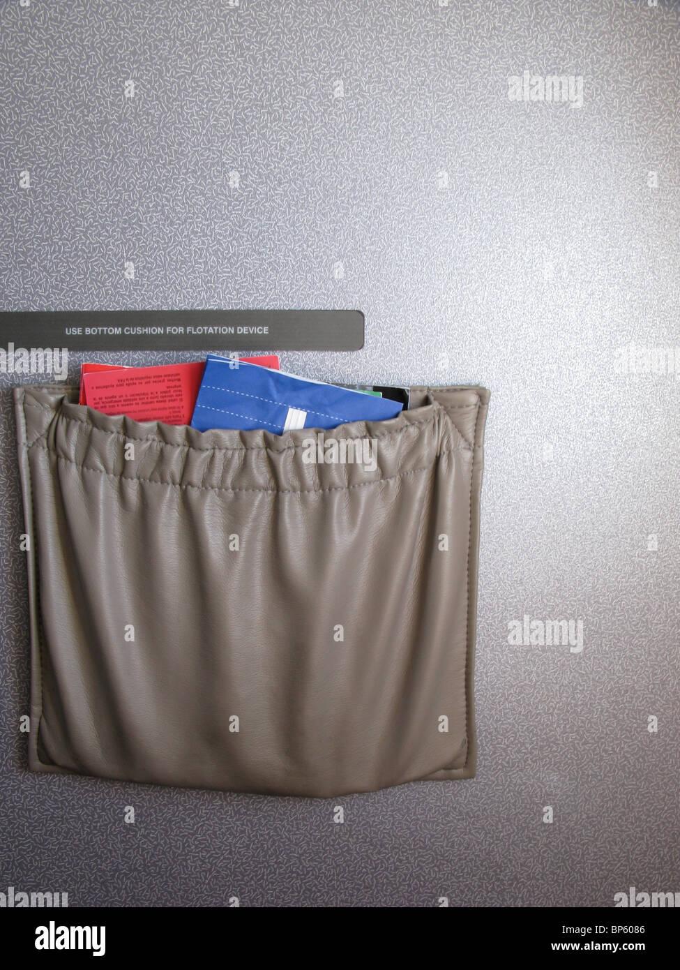 Les sièges des poches d'un avion contenant des instructions d'urgence, un magazine en vol et un sac Photo Stock