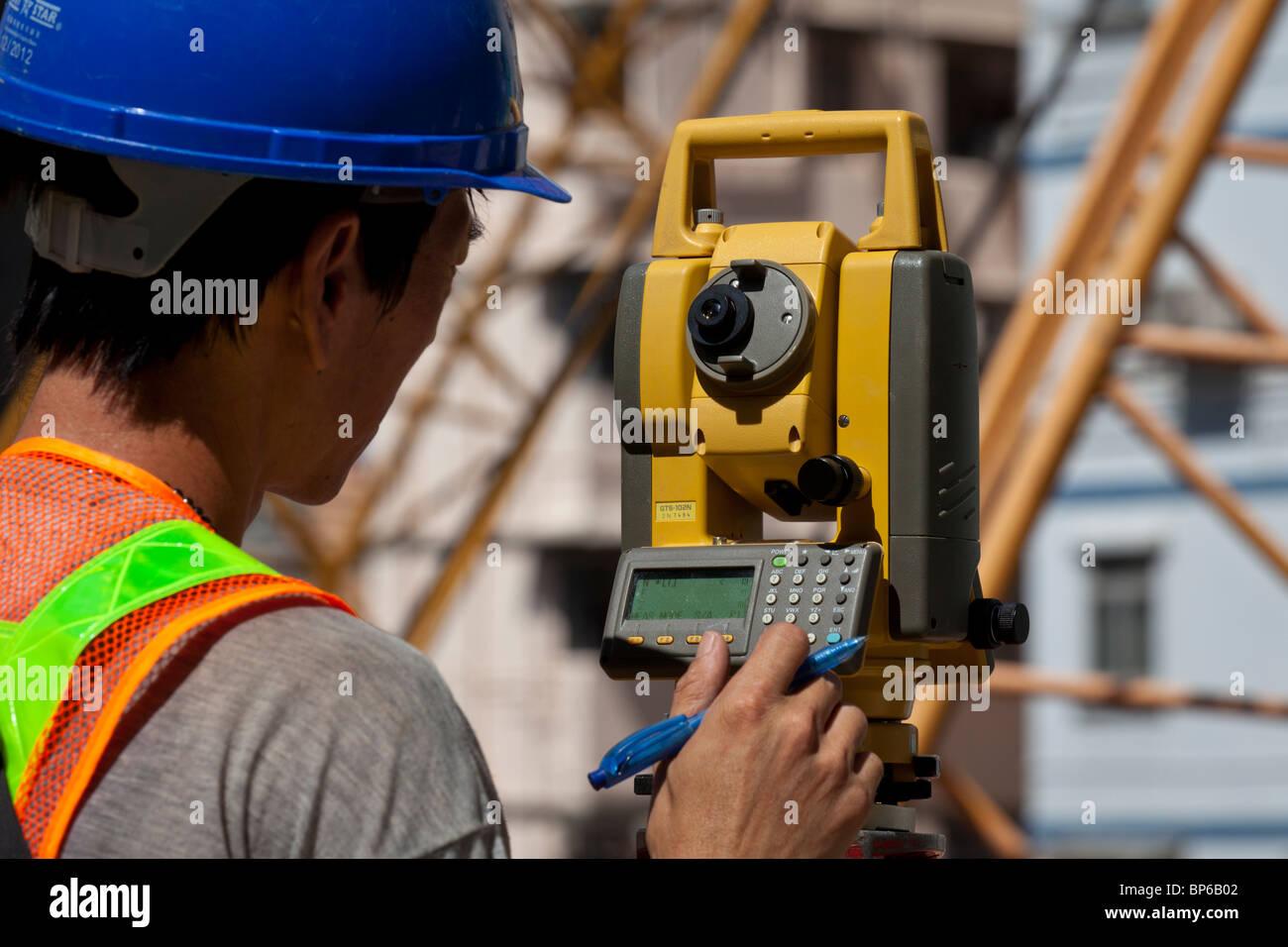 Un ingénieur prendre des lectures d'un théodolite, sur un site de construction à Hong Kong. Photo Stock