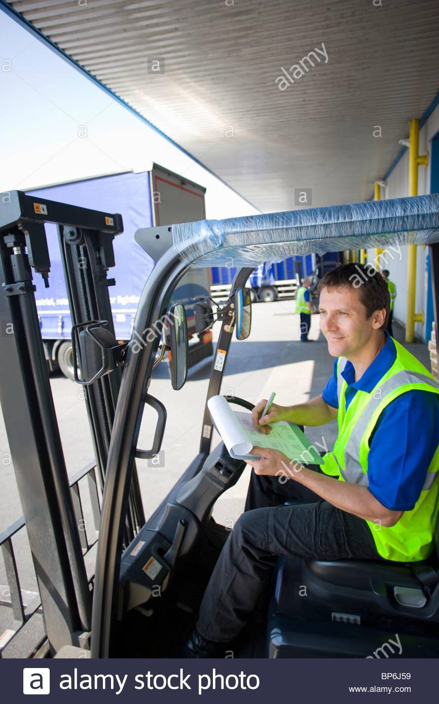 Travailleur en chariot élévateur writing on clipboard sur quai de chargement Photo Stock