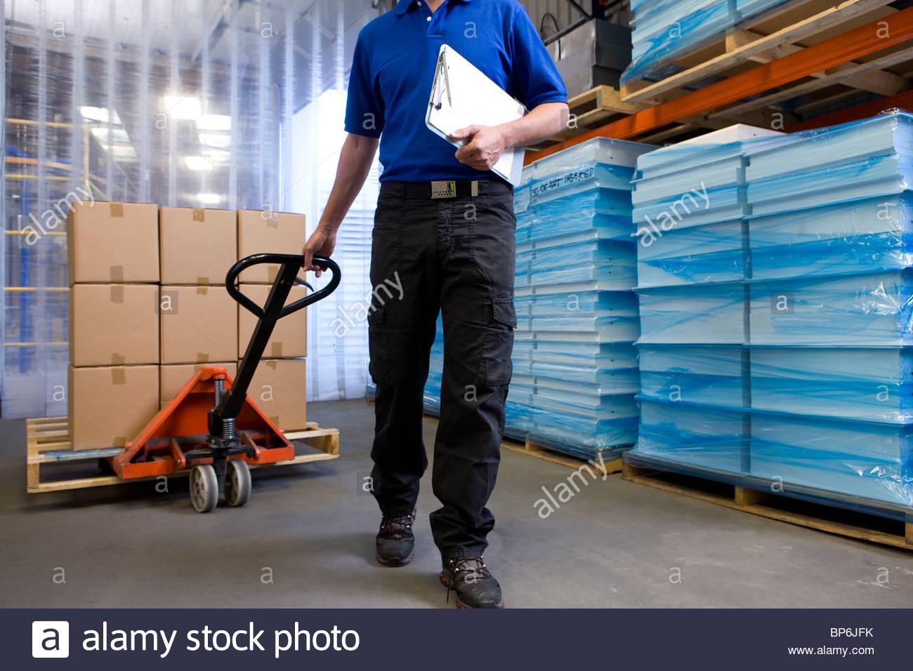 Travailleur sur quai de chargement de camion de main en tirant sur l'inventaire Photo Stock