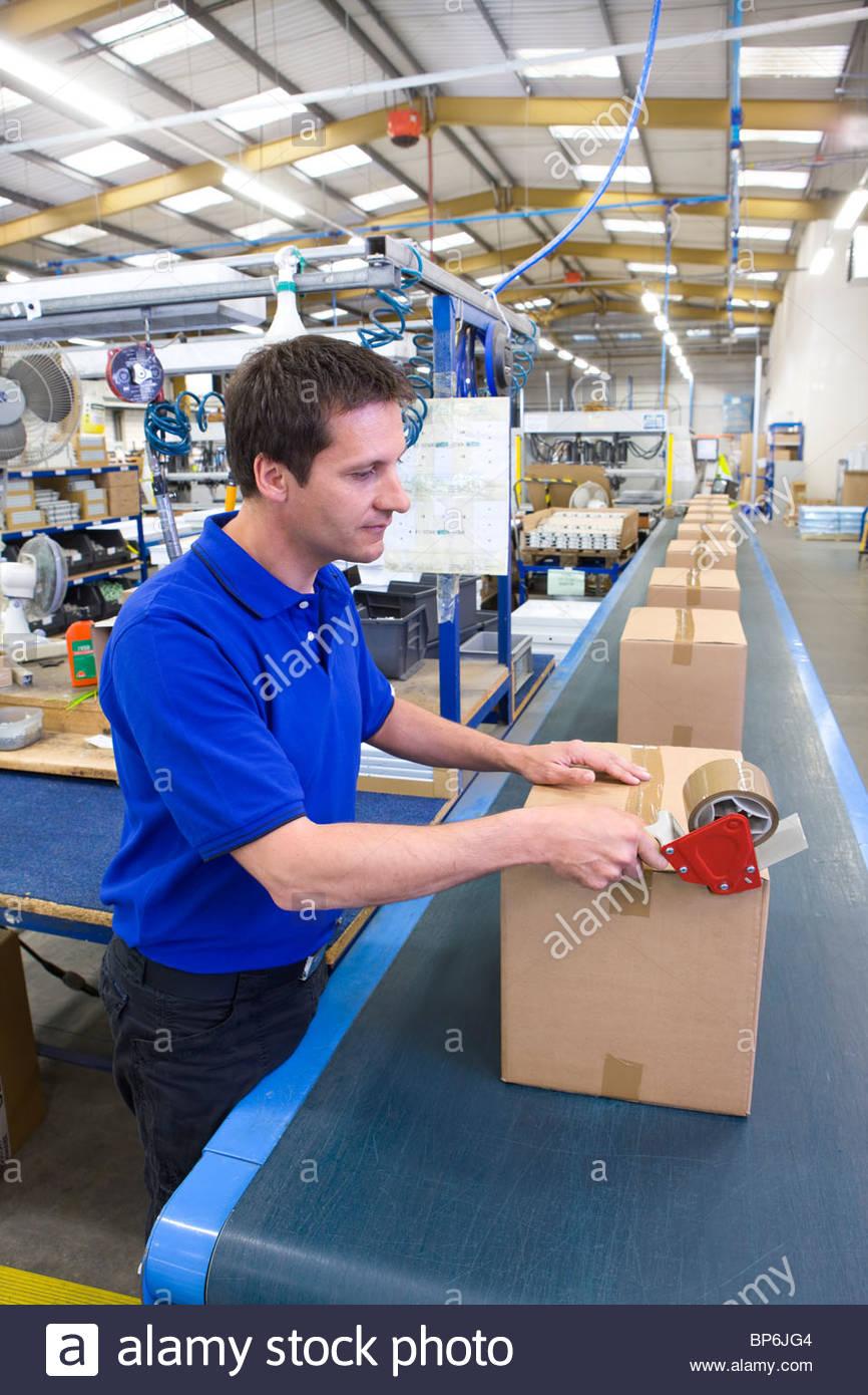 Travailleur dans l'entrepôt sur ligne de montage taping cardboard box Photo Stock