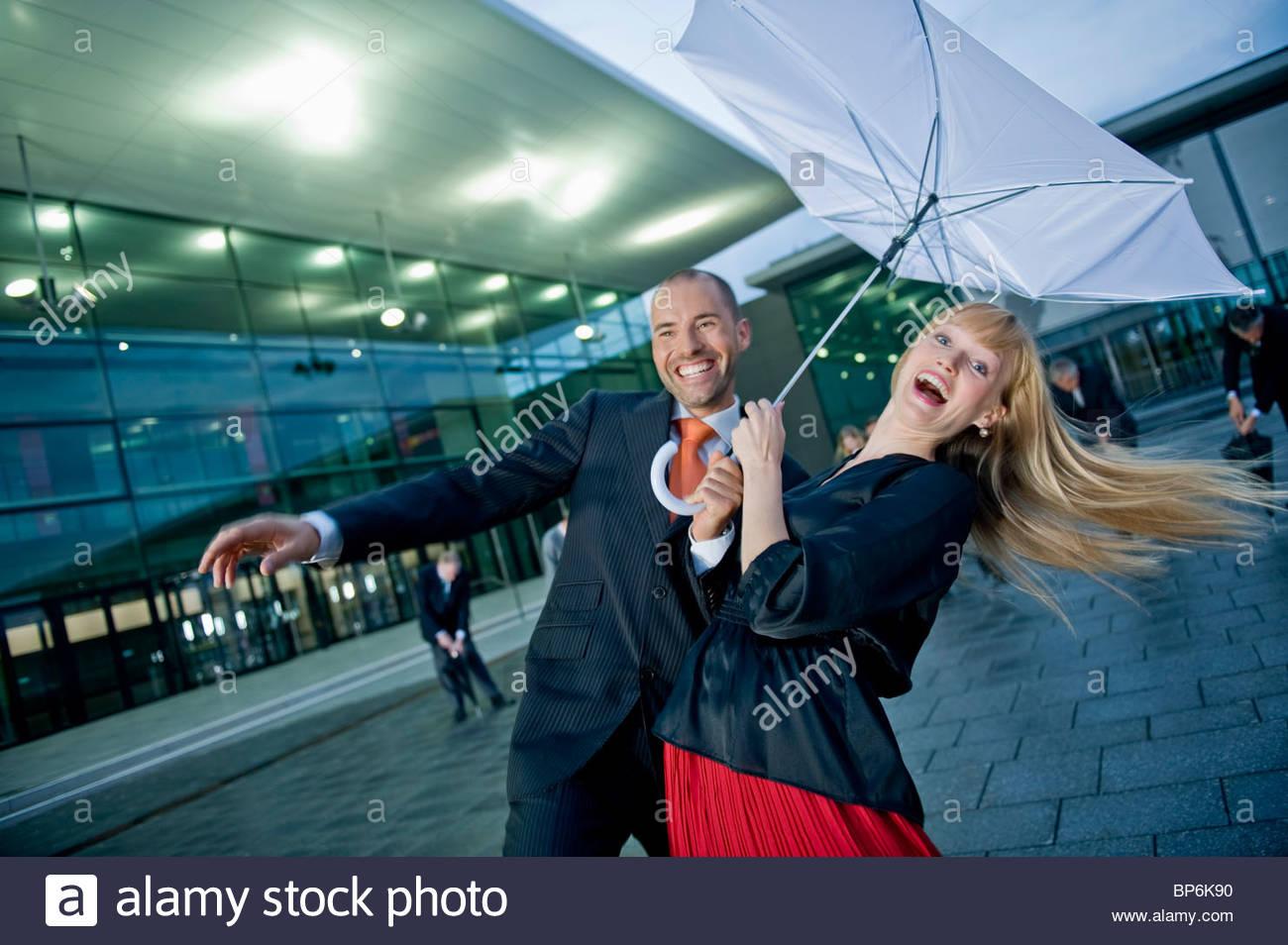 Un businessman and businesswoman holding un parapluie dans le vent fort Photo Stock