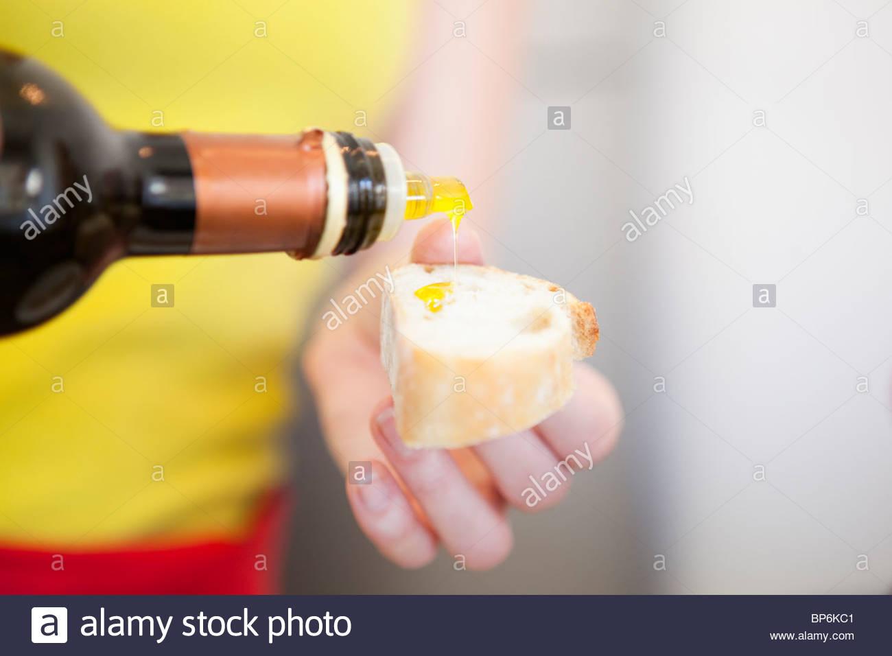 Un woman pouring olive oil sur un morceau de pain, close-up Photo Stock