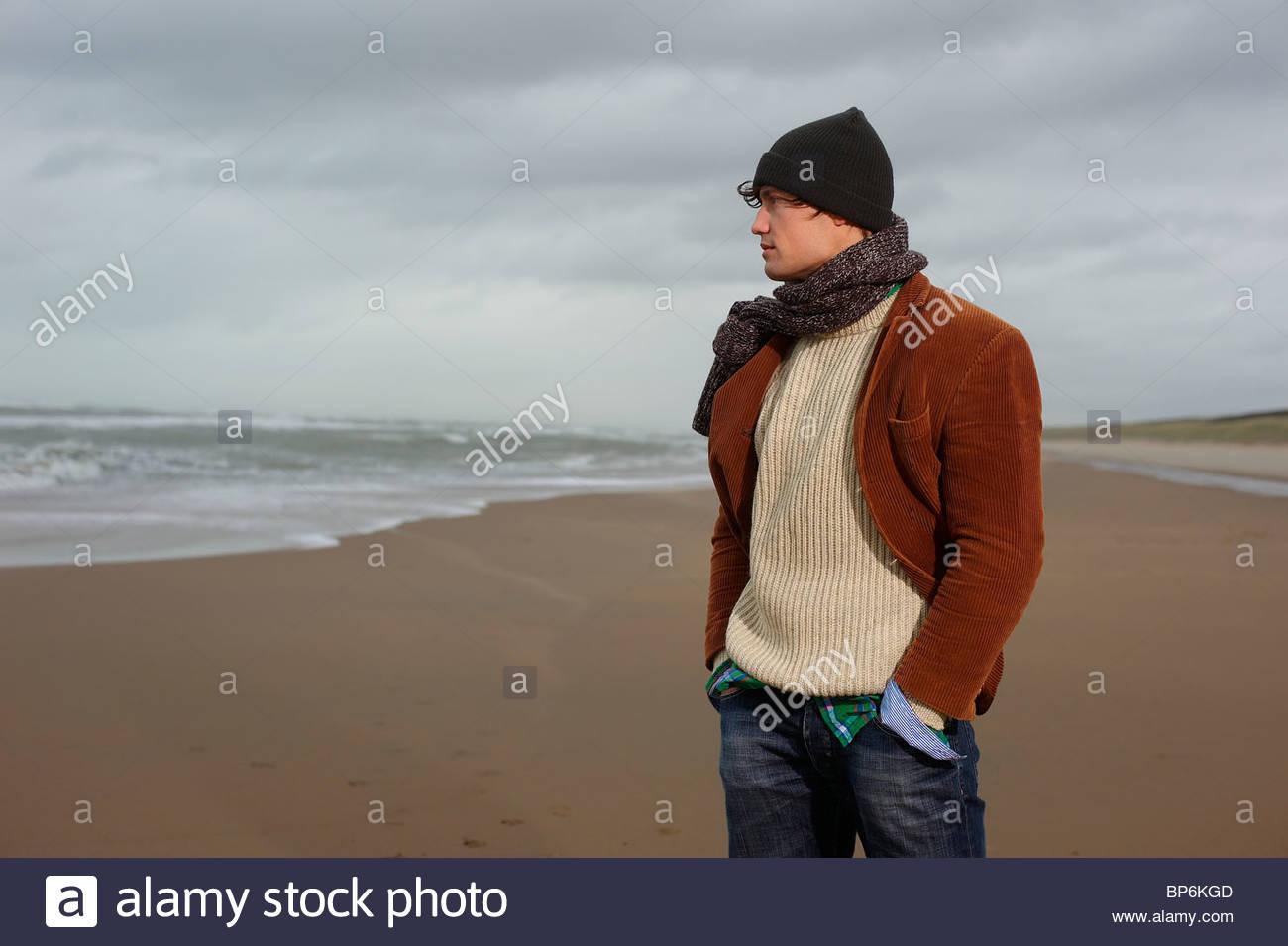 Un homme debout sur une plage sur une journée l'hiver à la mer Photo Stock