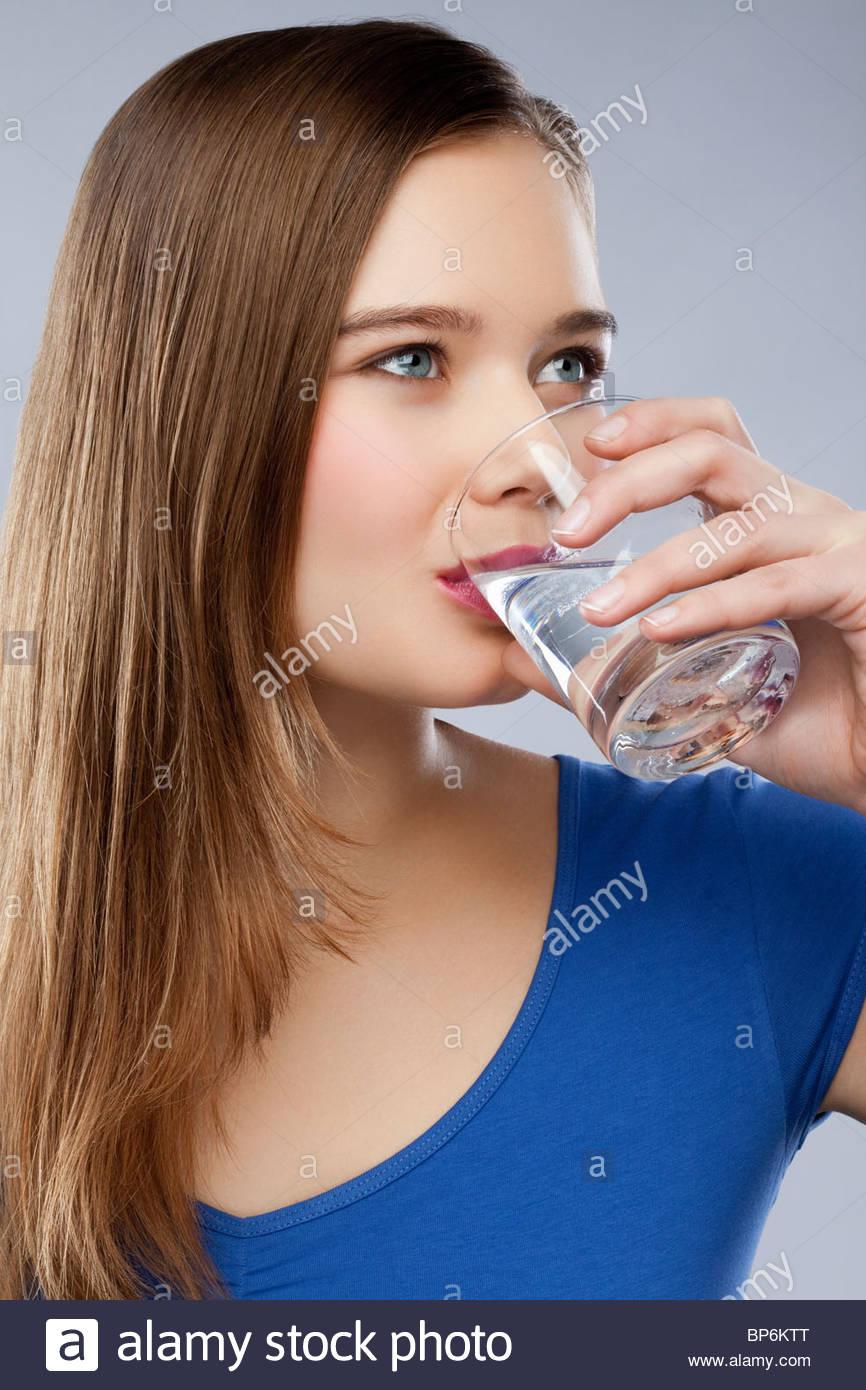 Une femme de boire un verre d'eau Photo Stock