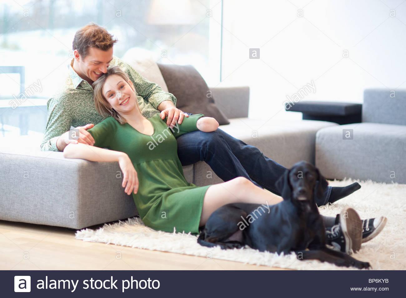 Jeune couple assis dans la salle de séjour avec chien, femme avec bras amputé Photo Stock
