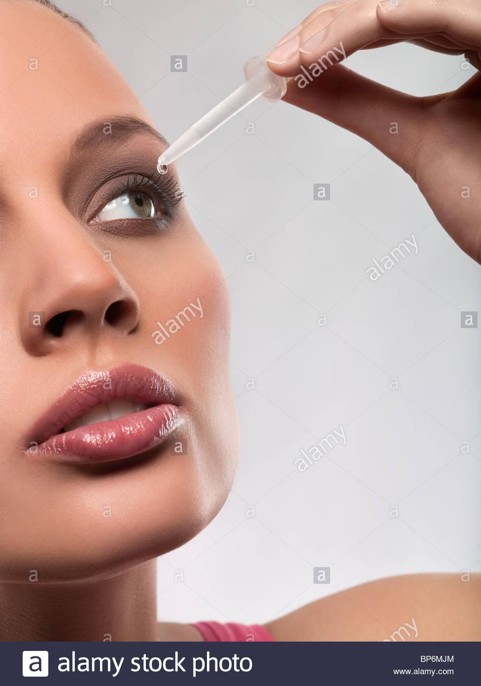 Jeune femme de mettre des gouttes dans l'oeil, studio shot Photo Stock
