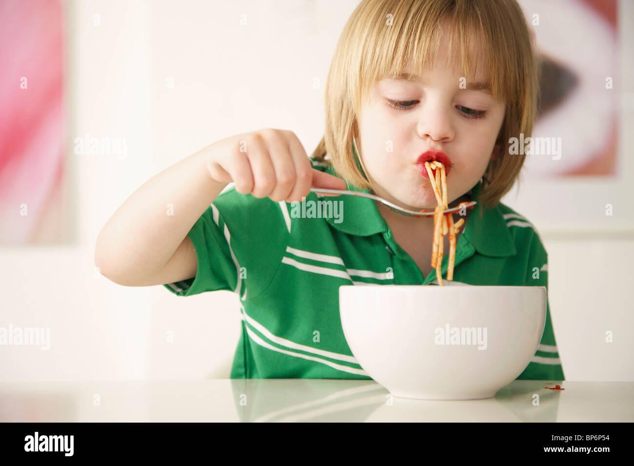 Un garçon mange du spaghetti Photo Stock