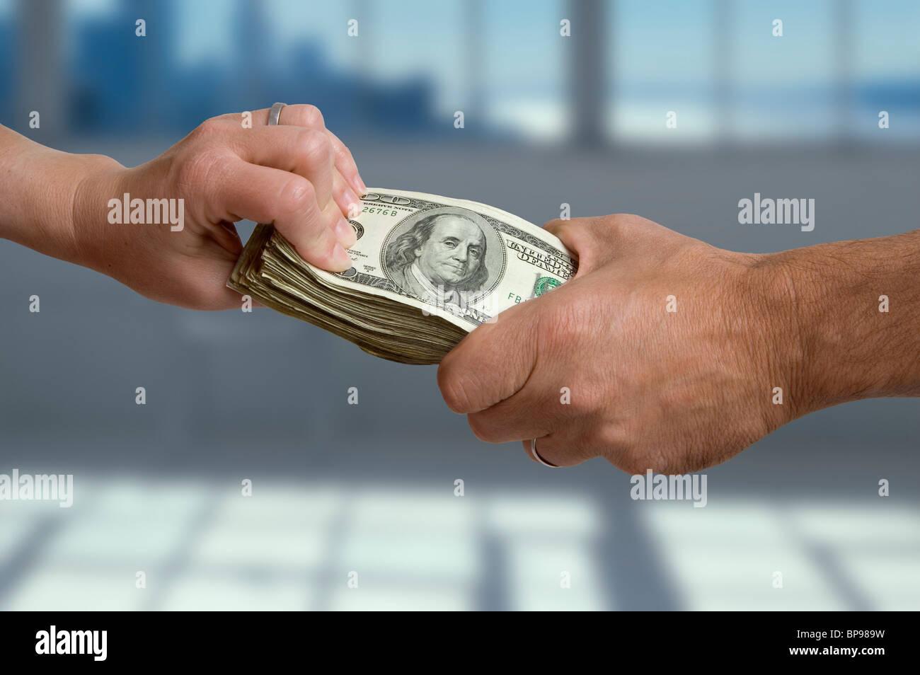 Un homme et femme de chaque main tenant à une pile d'argent comptant. Banque D'Images