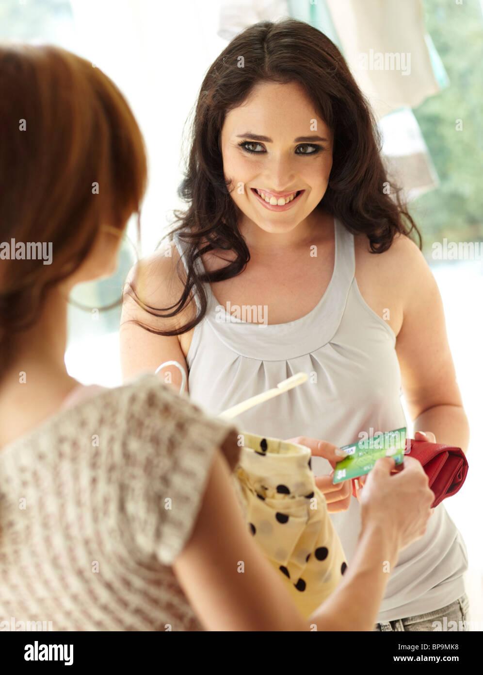 Jeune brunette femme de payer pour les marchandises en boutique Photo Stock