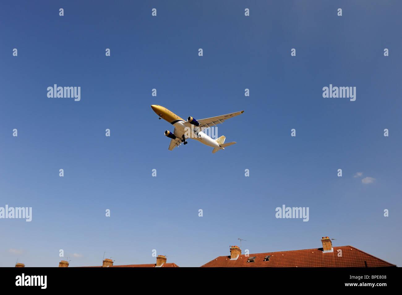 Gulf Air vol d'un avion à basse altitude au-dessus house avant l'atterrissage Banque D'Images