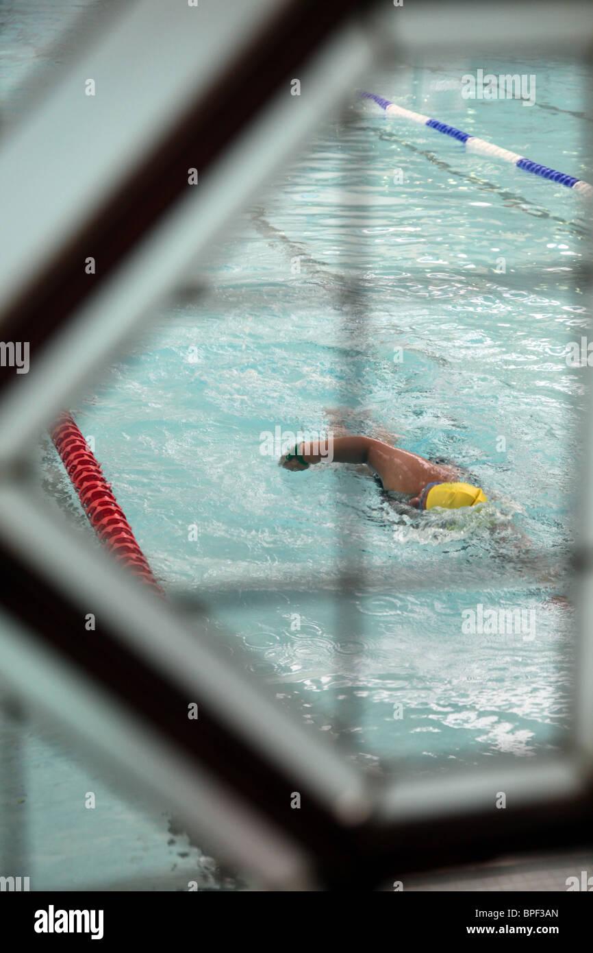 Un nageur anonyme exerçant dans une piscine vu à travers une fenêtre en verre. Photo Stock