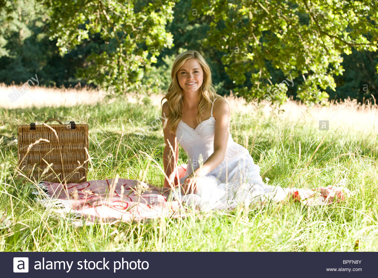 Une jeune femme assise sur une couverture de pique-nique Photo Stock