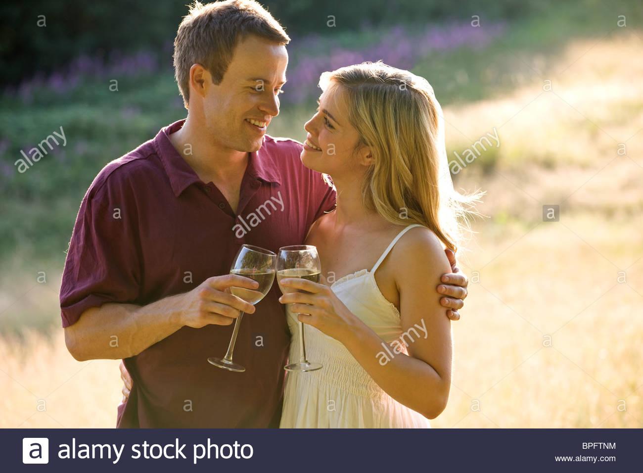 Portrait d'un jeune couple de boire du vin, se regardant amoureusement Photo Stock