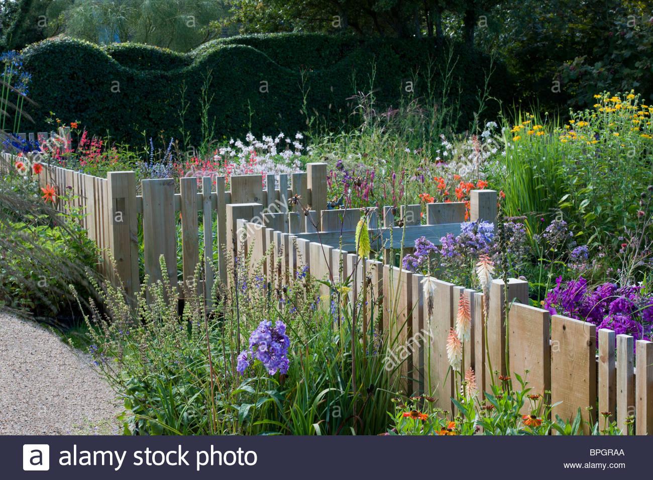Petit jardin clôture en bois clôtures flowling inhabituelle des largeurs variées de fleurs d'été Photo Stock