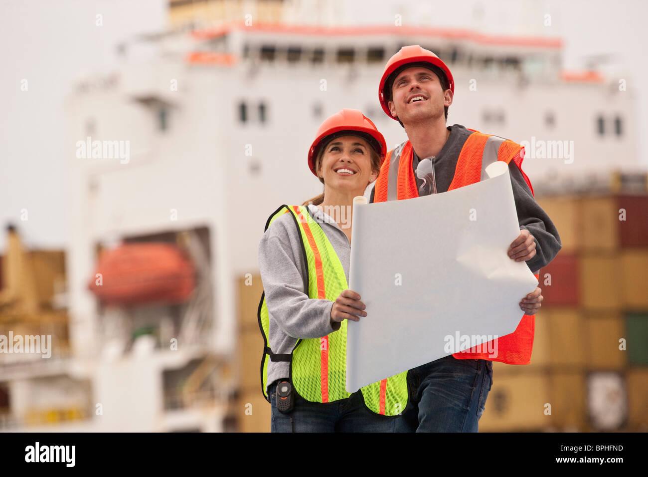 Les ingénieurs des transports holding a blueprint and smiling Photo Stock