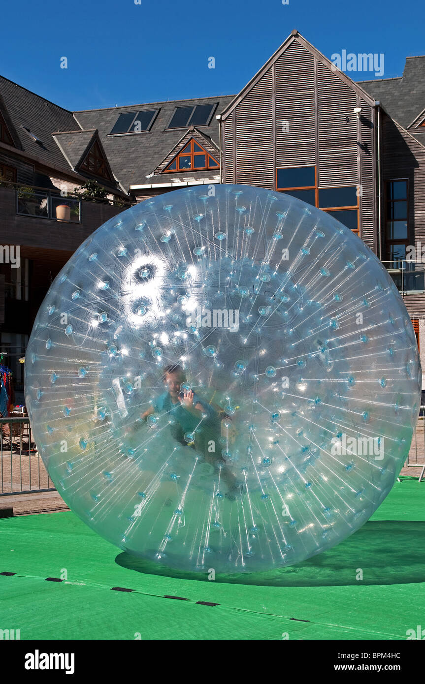"""Un jeune garçon """"zorbing"""" ' ' d'une gigantesque bulle en plastique Photo Stock"""