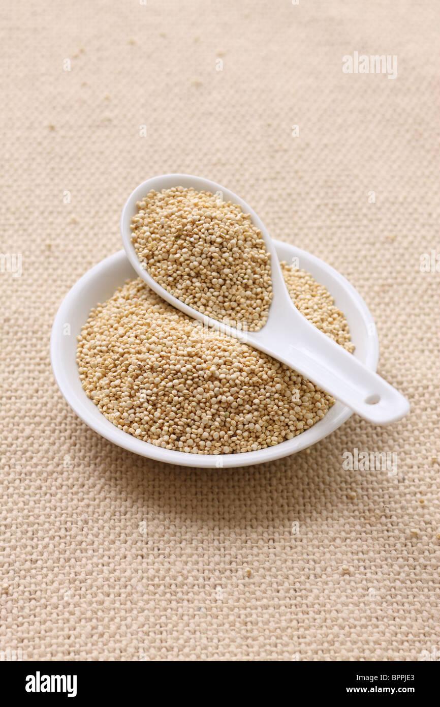 Le quinoa dans un petit bol et cuillère Photo Stock