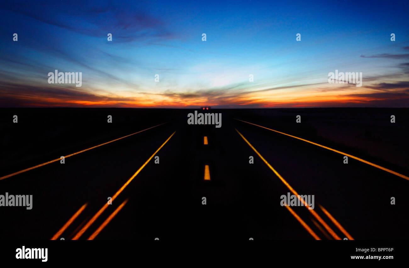 La route de nuit avec ciel dramatique et de voiture en mouvement Photo Stock