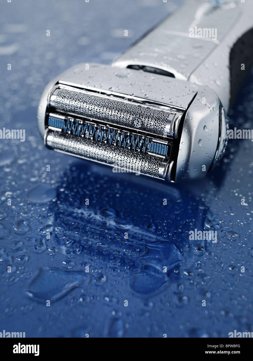 Braun 790CC - Rasoir électrique Pulsonic 9595 sur fond de verre bleu humide avec de l'eau tombe sur elle Photo Stock
