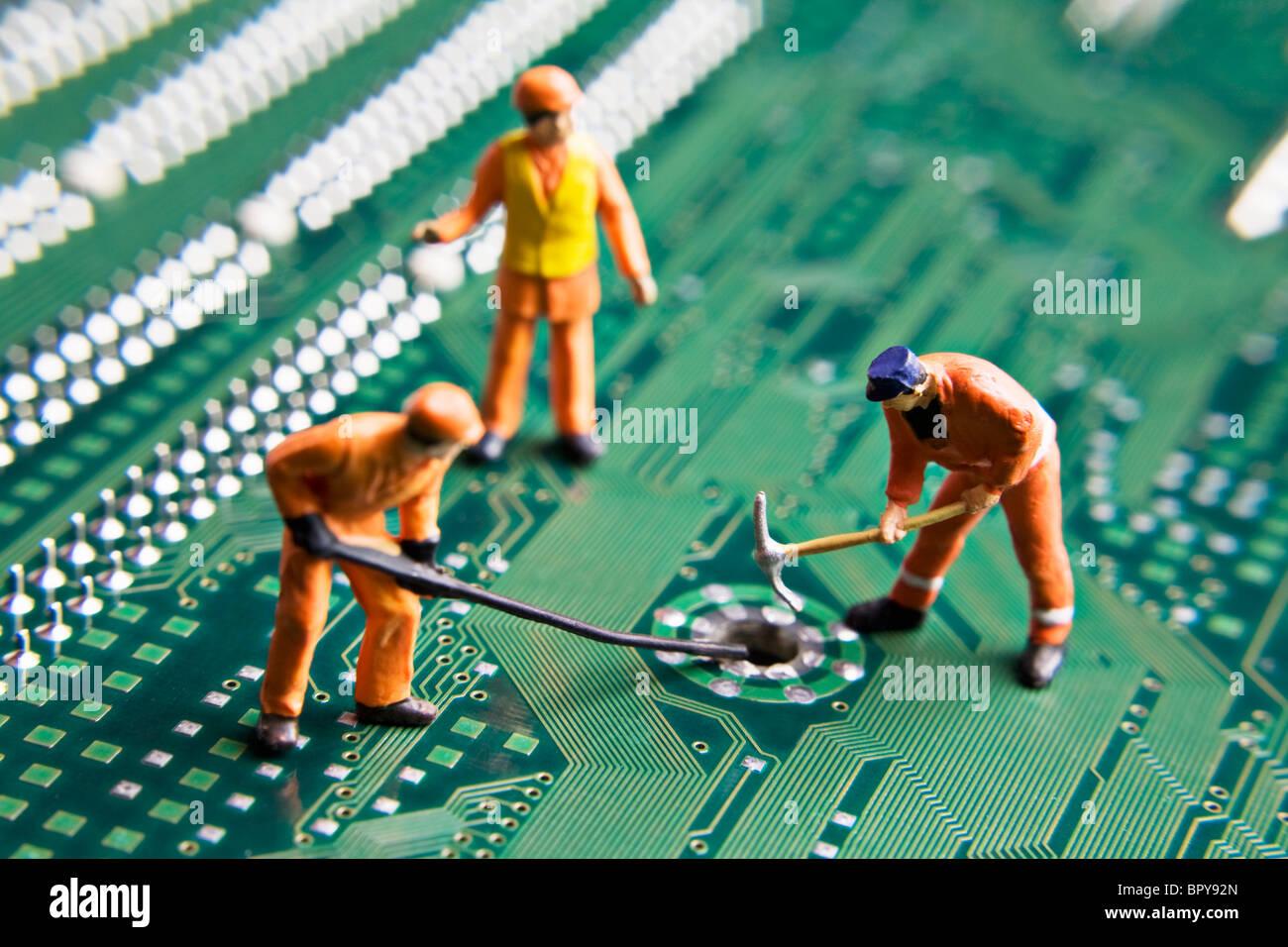 Figurines travailleur placé sur une carte de circuit imprimé Photo Stock