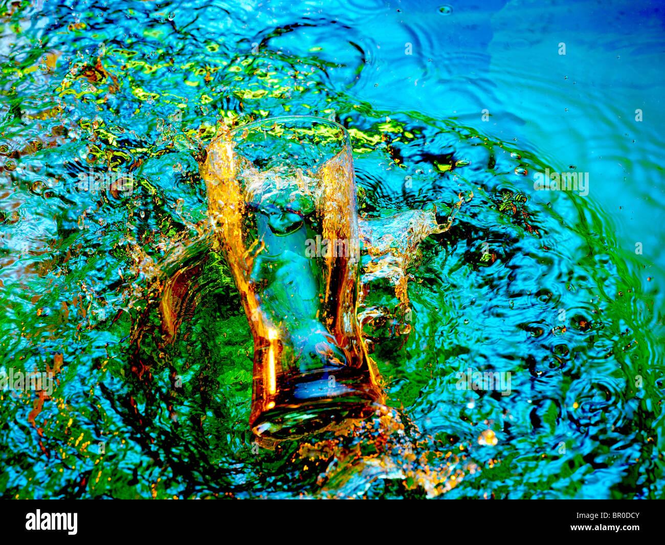 Le verre, splash, et les filigranes dans l'eau multicolore Photo Stock
