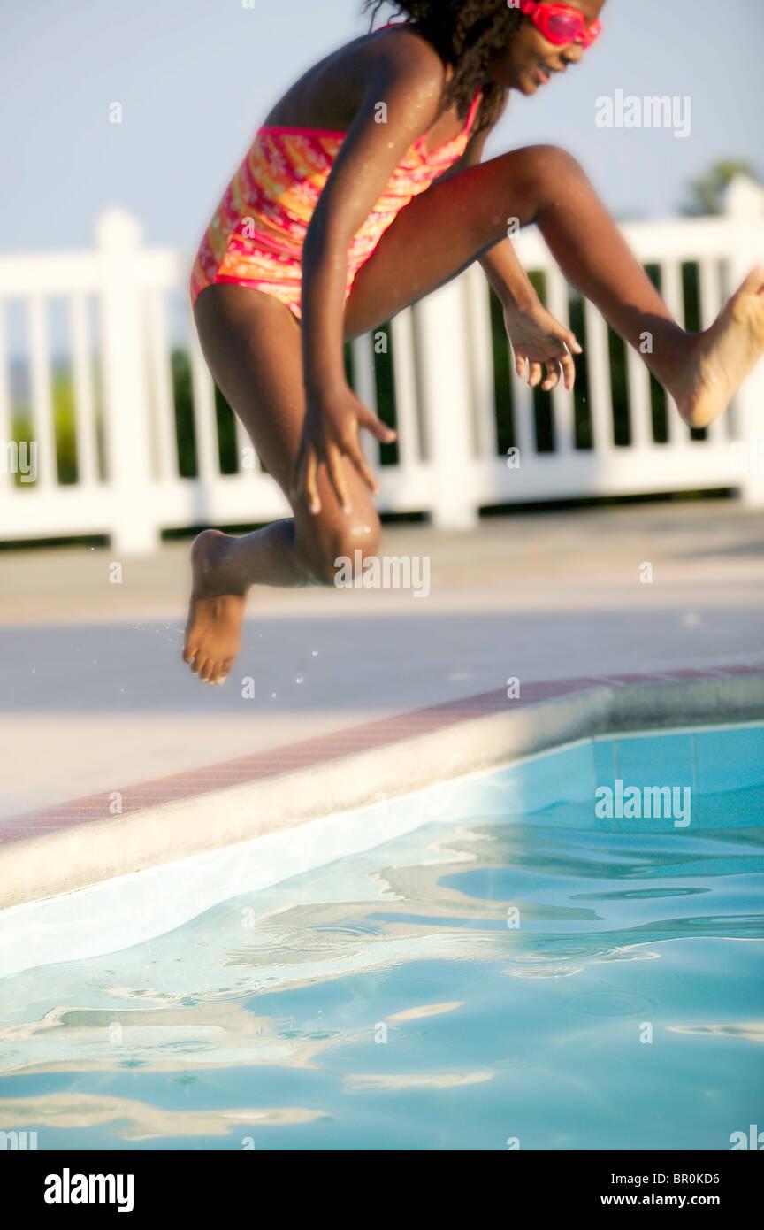 African American girl de sauter dans une piscine. Banque D'Images