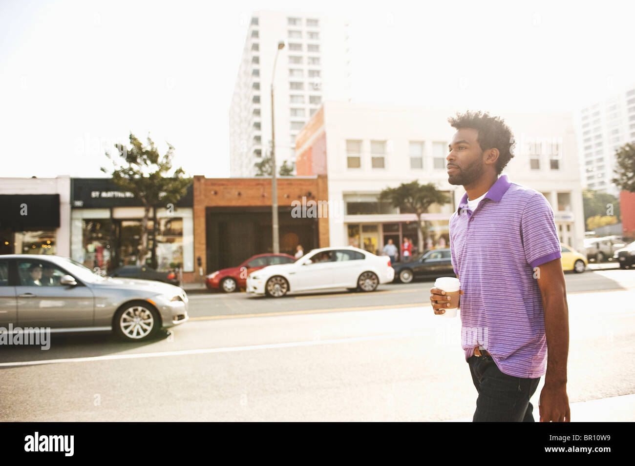 African American man with coffee cup walking on sidewalk Banque D'Images