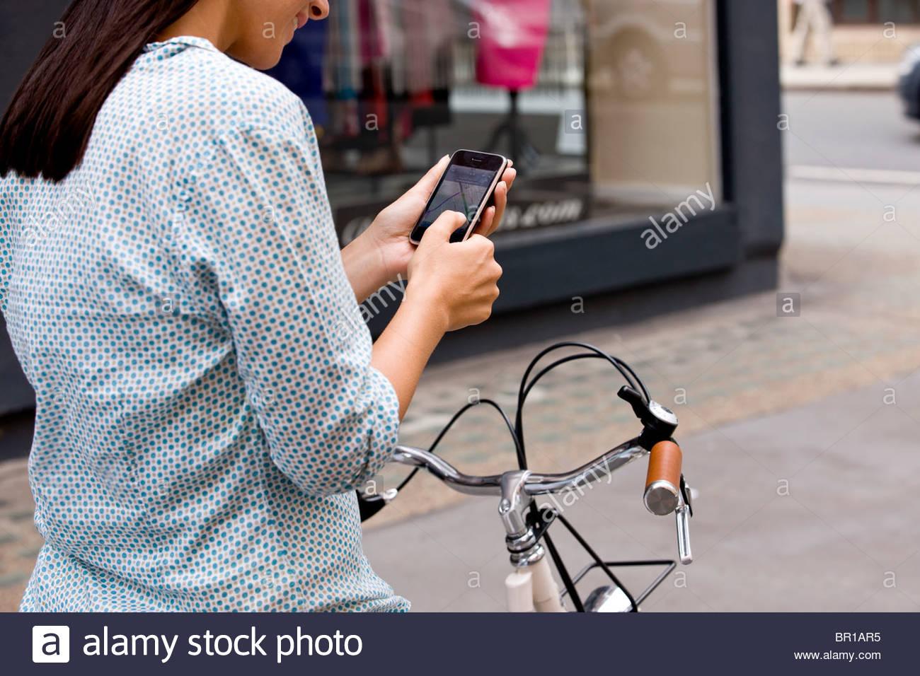 Une jeune femme sur un vélo, en regardant une carte sur son téléphone portable Photo Stock