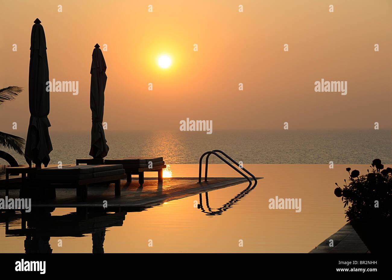 Piscine à débordement de l'hôtel au coucher du soleil, Kovalam, Kerala, Inde Photo Stock
