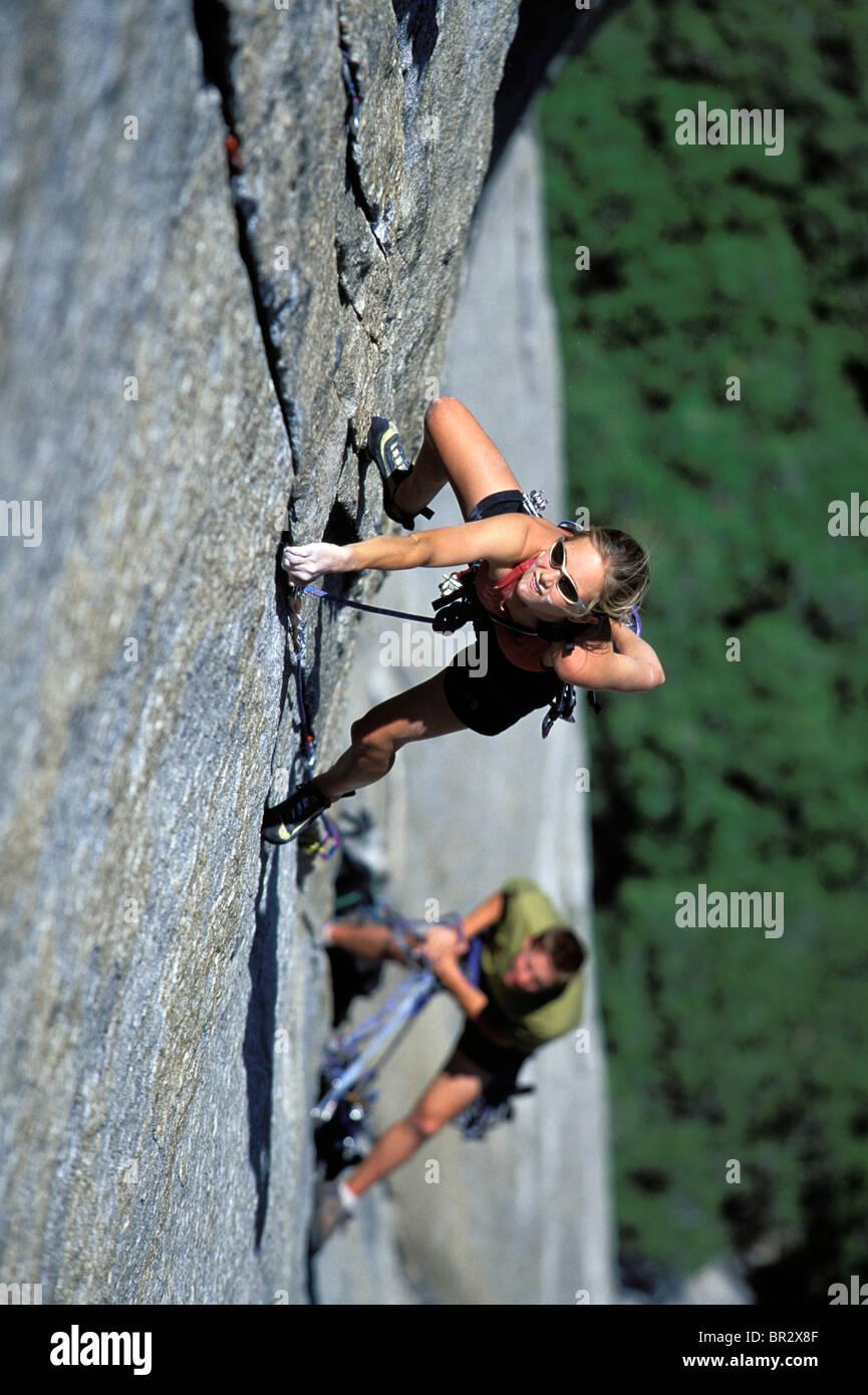 Escalade de femme sur un grand mur (high angle perspective). Photo Stock