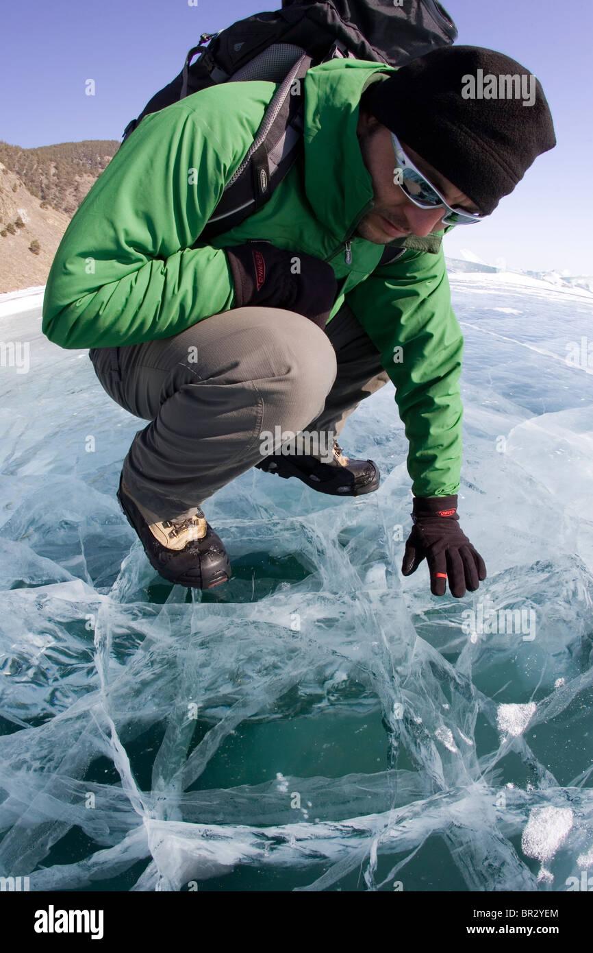 Un randonneur examine le Lac Baïkal gelé pendant l'hiver en Sibérie, Russie. Photo Stock