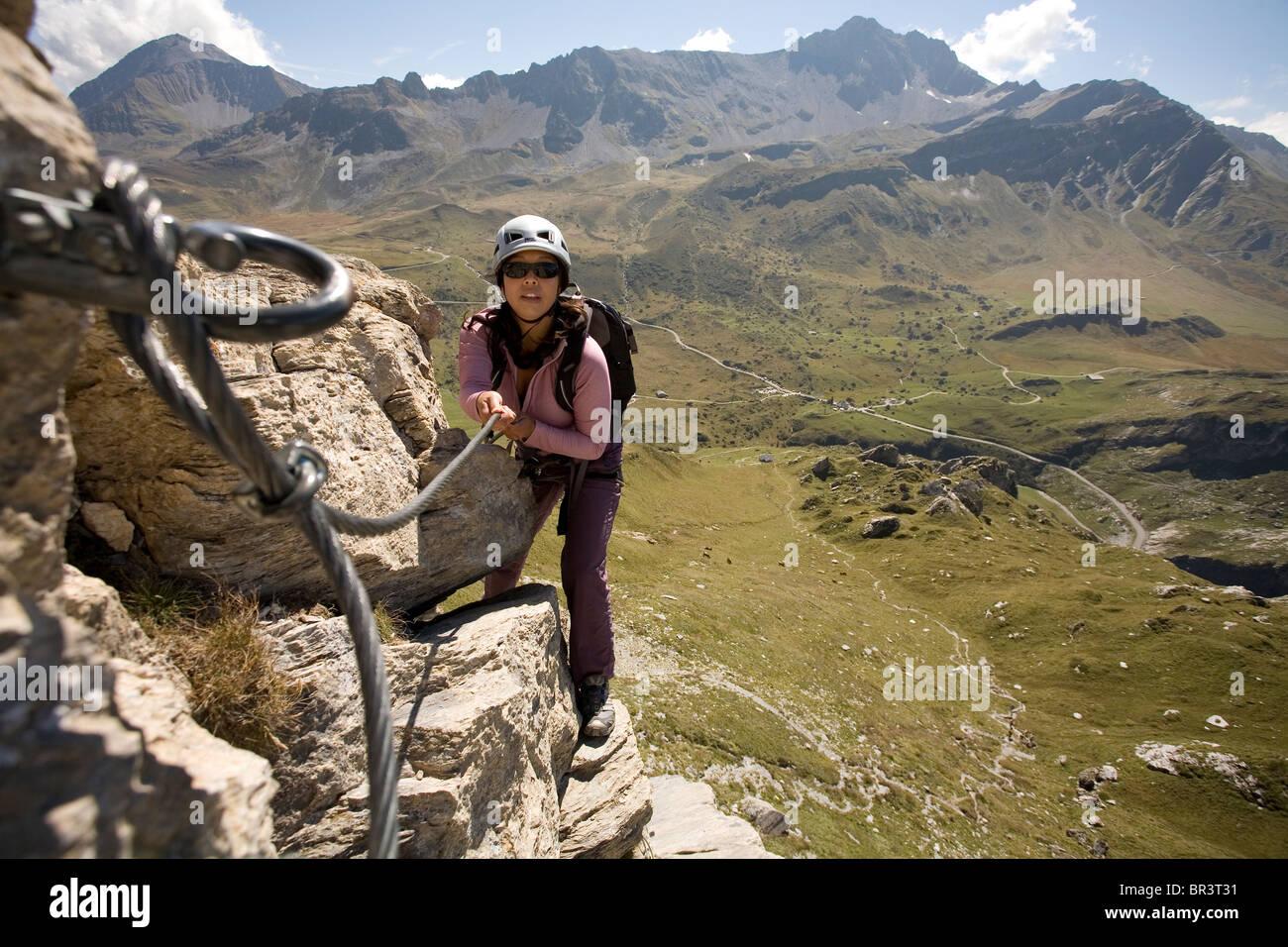 Une jeune femme utilise le câble vissé sur le rocher d'escalade pour soutenir tout en s'engageant Photo Stock