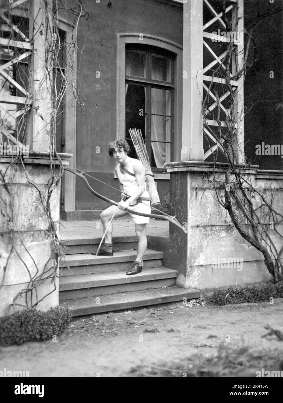 Image historique, garçon avec un arc et une flèche, ca. 1920 Photo Stock