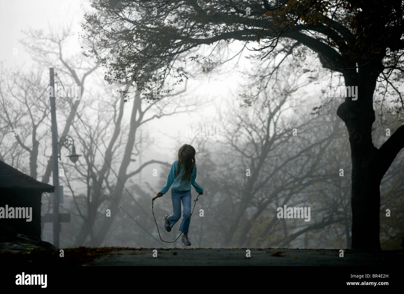 Une jeune fille saute à la corde. Photo Stock