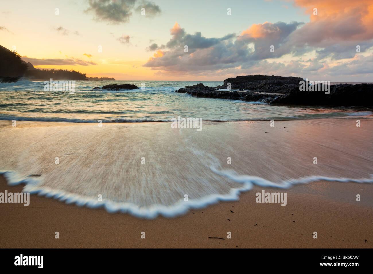 Kauai, HI Soir lumière sur Lumaha j'Beach avec des couleurs de ciel reflétant sur les vagues Photo Stock