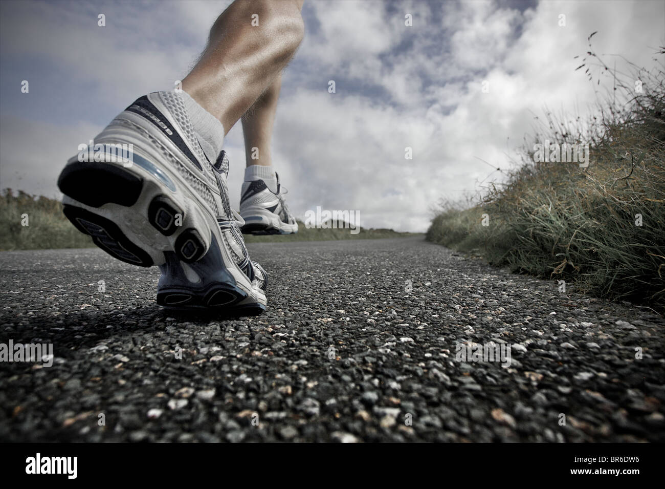 Un proche, low angle view of a male athlete running le long d'une route goudronnée avec ses grandes jambes Photo Stock