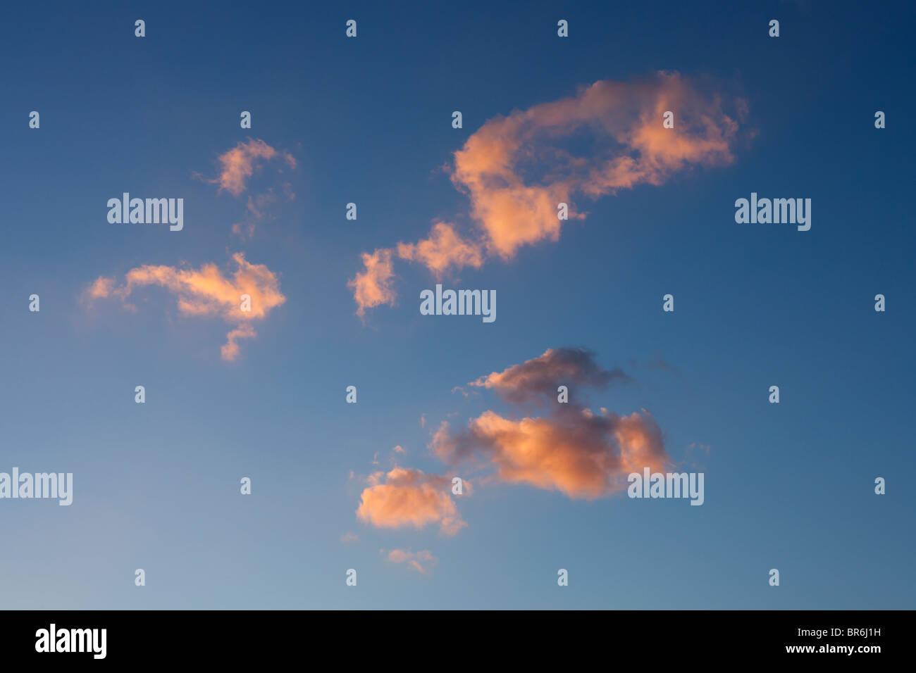 Quelques nuages se dissipant allumé au coucher du soleil. Photo Stock
