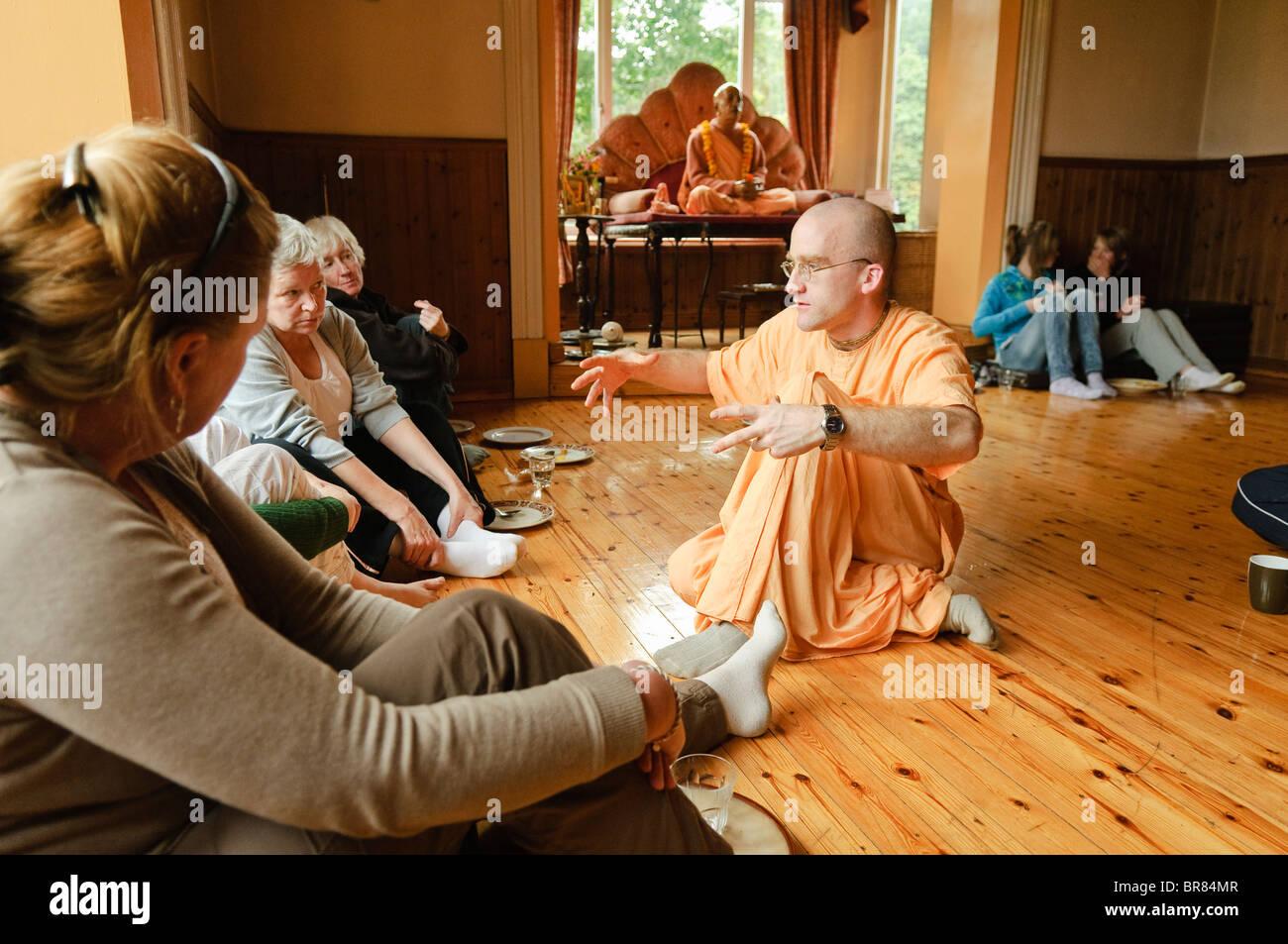 Dévot Hare Krishna portant robe safran explique sa religion à ses invités dans une salle du temple Hare Krishna Banque D'Images