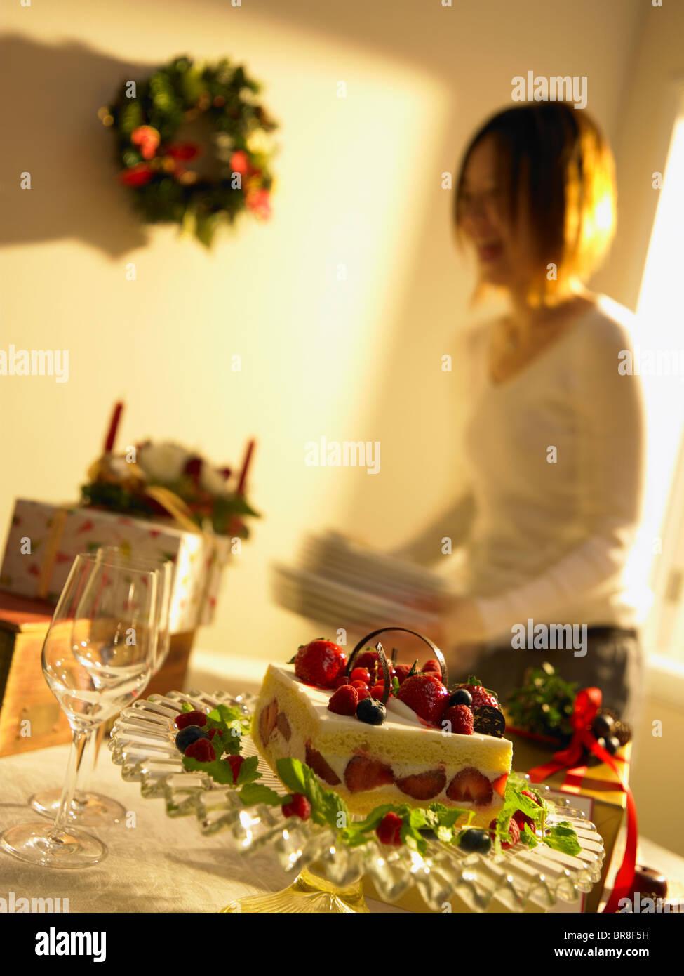 Gâteau de Noël sur la table, woman holding les plaques à l'arrière-plan, blurred motion Banque D'Images