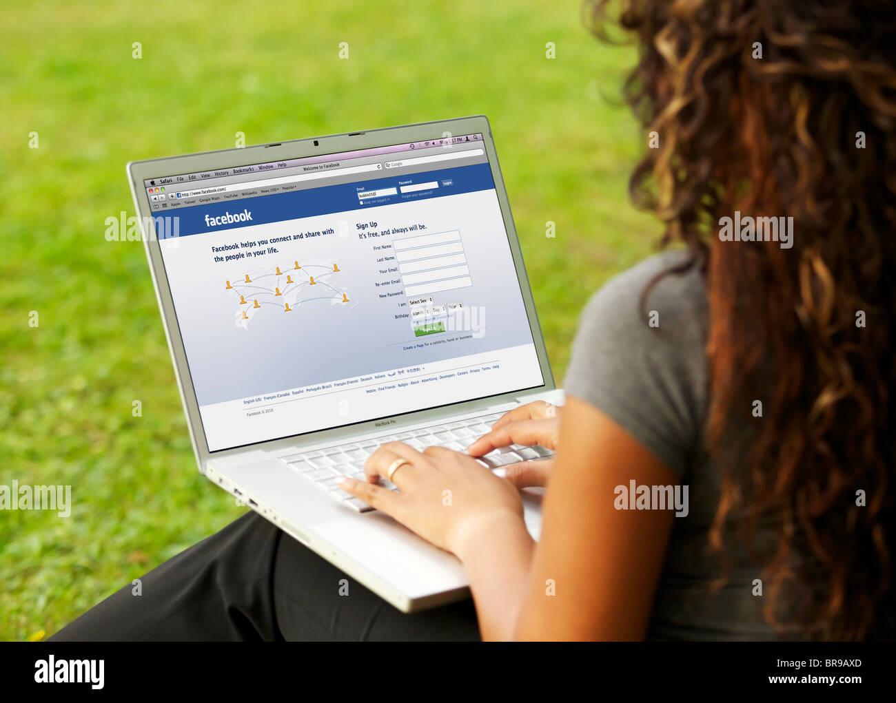 Jeune femme en signature sur sa page Facebook en ligne sur un seul ordinateur portable au parc Photo Stock